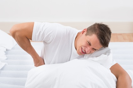 Young Man On Bed Suffering From Backache