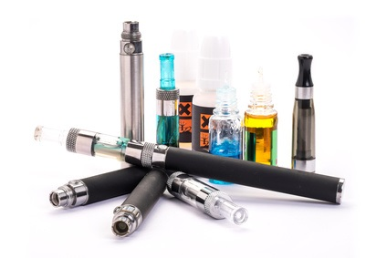 Group of electronic cigarette nicotine inhalator ,bottles with liquids behind the inhalator. isolated on white background