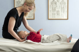 Female osteopath treating toddler