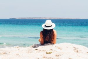 A woman in a straw hat reclines on a white sand beach in front of an azure ocean - going on holiday when you have ME, Chronic Fatigue or Fibromyalgia