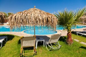 A couple of sunloungers under a palm leaf umbrella beside a turquoise swimming pool - how to ask for what you need when on holiday with ME, CFS or Fibromyalgia