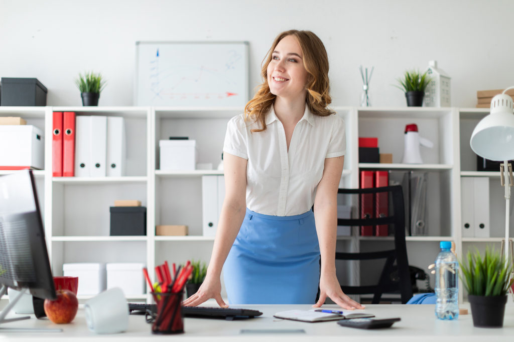 Woman standing behind desk at work